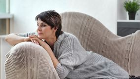 Melancholic beautiful mature woman in warm clothes relaxing on couch at cozy home interior. Medium shot. Pensive charming female in woolen shawl dreaming and stock video footage