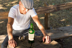 Melancholic drunk man with a bottle of white wine Royalty Free Stock Image