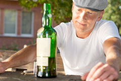 Melancholic drunk man looking at a bottle Royalty Free Stock Photo