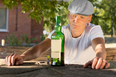 Melancholic drunk man looking at a bottle of wine Stock Image