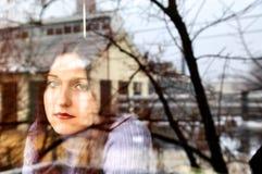 Melancholic Frau am Fenster. Stockfotografie