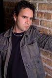Melancholic Male Portrait. Melancholic portrait of man on brick wall stock image