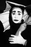 Melancholic mime with umbrella. Melancholic actor-mime in dramatic makeup with umbrella. Black and white photo Stock Photos