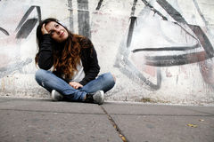 Melancholic Music. A young woman listening to melancholic Music and sitting on the pavement Royalty Free Stock Image