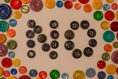 Melancholic, pessimist. Boredom among the general fun, life in black, negative mood, depression. Bright background of colored buttons for clothes, in the middle Royalty Free Stock Photos