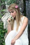 Melancholic portrait of cute blonde woman smelling flowers Stock Photo