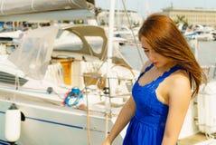 Melancholic woman in dress walking on marina Royalty Free Stock Image
