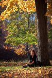 Melancholic woman rests under a tree Stock Photo