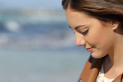 Melancholic woman thinking on the beach. Close up portrait of a melancholic woman thinking on the beach with the sea in the background Stock Photo