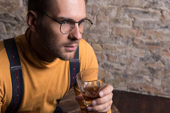 Melancholic youthful man in glasses sorrowfully pondering Stock Photos