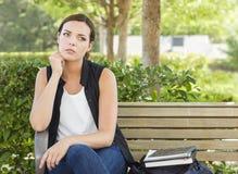 Melancholische junge erwachsene Frau, die auf Bank nahe bei Büchern sitzt Stockfoto