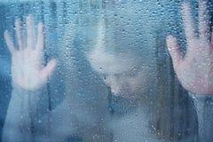 Melancholische und traurige junge Frau am Fenster im Regen Stockfotografie