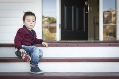 Melancholischer Mischrasse-Junge, der auf Front Porch Steps sitzt Lizenzfreies Stockfoto