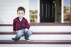 Melancholischer Mischrasse-Junge, der auf Front Porch Steps sitzt Lizenzfreie Stockbilder