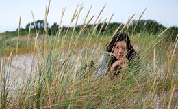 Melancholy. A view of a melancholy young woman lying on the grass Royalty Free Stock Photography
