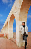 Melancholy. Pretty lonely girl standing under the arches of the ancient arches Royalty Free Stock Photos