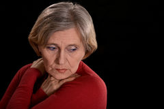 Melancholy elderly woman. In red on a black background Stock Photo