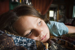 Melancholy Girl. Girl laying on bed contemplating Einsteins theory of relativity Stock Photography