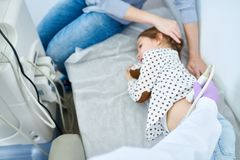 Melancholy little girl lying on side on medical couch stock photos