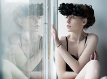 Melancholy - lovely girl sitting by the window Stock Photo