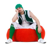 Melancholy man dressed like a gnome sitting on red Royalty Free Stock Photography