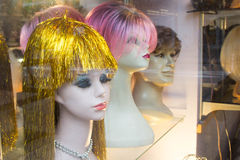 Melancholy mannequin heads with Funky Wigs. Three melancholy mannequin heads in a store window, with funky bright colored wigs stock photography
