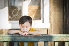 Melancholy Mixed Race Boy Leaning on Railing Stock Photos
