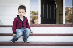 Melancholy Mixed Race Boy Sitting on Front Porch Steps Stock Photo