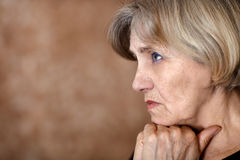 Melancholy older woman. Portrait of melancholy older woman on a beige background Stock Image