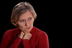 Melancholy older woman. In red on a black background Royalty Free Stock Image