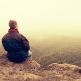 Melancholy and sad day. Man at enge of rock above deep vally.  Tourist on the peak of sandstone rock watching to mist. Royalty Free Stock Images
