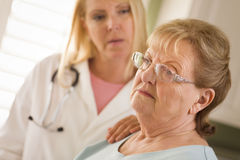 Senior Adult Woman Being Consoled by Female Doctor or Nurse Royalty Free Stock Image