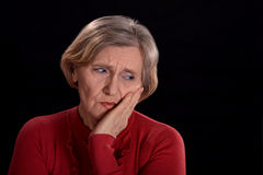 Melancholy senior woman. In red on a black background Stock Photography