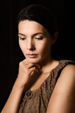 Melancholy woman with a serious expression. Melancholy depressed young woman with a serious expression and downcast eyes standing thinking in a deep royalty free stock image