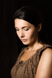 Melancholy woman with a serious expression. Melancholy depressed young woman with a serious expression and downcast eyes standing thinking in a deep stock photo