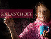 Melancholy written on virtual screen. young woman melancholy and sad at the window in the rain, she holding a cup of hot. Coffee or tea Royalty Free Stock Photo