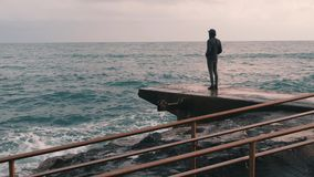 Melancholy young boy standing at pier. Lonely boy looking at rainy stormy sea. Pessimistic man at sea marina. Young boy in dark we. Ar standing at seacoast stock footage
