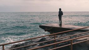 Melancholy young boy standing at pier. Lonely boy looking at rainy stormy sea. Pessimistic man at sea marina. Young boy in dark we. Ar standing at seacoast. Big stock video