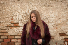 Melancholy young girl with red fur coat Royalty Free Stock Images