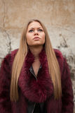 Melancholy young girl with red fur coat. Looking up royalty free stock photos