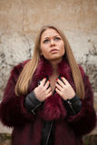Melancholy young girl with red fur coat Royalty Free Stock Image