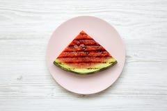 Melancia grelhada em uma placa cor-de-rosa sobre a superfície de madeira branca, de cima de Fruto saudável do verão Configuração  Imagens de Stock