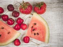 Melancia, morangos e cerejas no fundo de madeira Fotografia de Stock