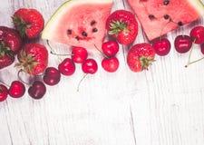 Melancia, morangos e cerejas no fundo de madeira Foto de Stock