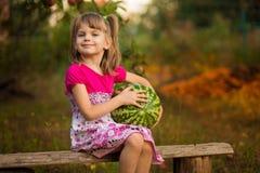 Melancia muito grande feliz da posse da menina da criança no dia ensolarado fotografia de stock royalty free
