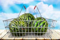 Melancias verdes no cesto de compras na tabela de madeira com fundo azul do bokeh do céu nebuloso Alimento orgânico do vegetarian Imagem de Stock