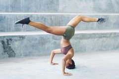 Melanesian athlete girl doing split upside down in headstand pose stock images