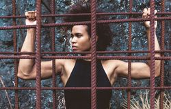 Athlete girl with strong arms after workout behind iron bars. Melanesian pacific islander athlete girl with strong arms after workout behind iron bars Royalty Free Stock Photos