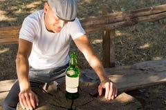 Melankolisk berusad man med en flaska av vitt vin royaltyfri bild