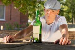 Melankolisk berusad man som ser en flaska av vin fotografering för bildbyråer